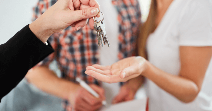 Renters receiving key to rental unit.